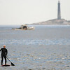 PAUL BILODEAU/Staff photo. A standup paddle boarder makes his way across the water near Good Harbor Beach  5/16/19