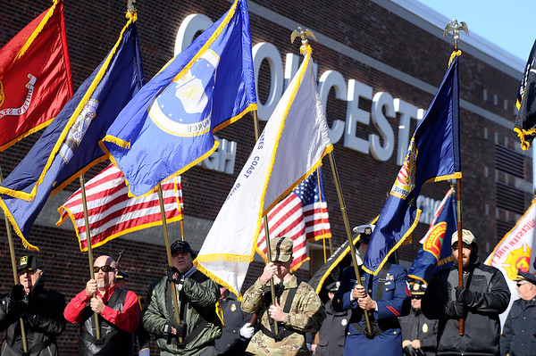 Flags are held high as the color guard steps off from Gloucester High for the parade to the American Legion during the Gloucester Veterens Day Ceremony and Parade on Sunday November 11, 2018.  Photo by Joseph PREZIOSO
