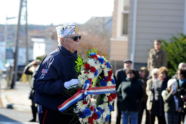 "Thomas Glenn carries a wreath to be laid at the WWI Joan of Arc Monument by the American Legion building during the Gloucester Veterens Day WWI Ceremony to honor the Gloucester soldiers who died during the ""Great War"" and remember the Armistice that was signed by the Allies and Germany 100 years ago to end the war on Sunday November 11, 2018.  Photo by Joseph PREZIOSO"
