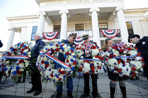 """Community members prepare the wreaths to be placed at the WWI Joan of Arc Monument by the American Legion building during the Gloucester Veterens Day WWI Ceremony to honor the Gloucester soldiers who died during the """"Great War"""" and remember the Armistice that was signed by the Allies and Germany 100 years ago to end the war on Sunday November 11, 2018.  Photo by Joseph PREZIOSO"""
