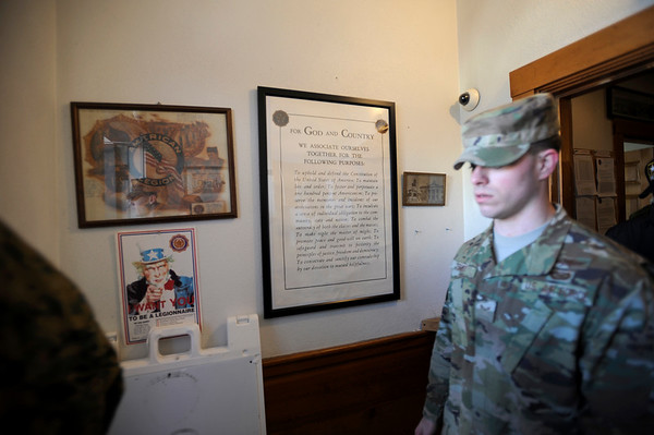 "A JROTC recruit walks by signs in the American Legion building during the Gloucester Veterens Day WWI Ceremony to honor the Gloucester soldiers who died during the ""Great War"" and remember the Armistice that was signed by the Allies and Germany 100 years ago to end the war on Sunday November 11, 2018.  Photo by Joseph PREZIOSO"