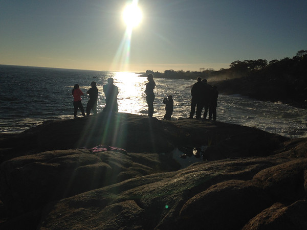 SEAN HORGAN/Staff photo<br /> Rescue personnel and others look for signs of fisherman Eduardo Correa of Swampscott was knocked off the rocks at Rafes Chasm in Gloucester on Tuesday afternoon.