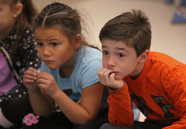 MIKE SPRINGER/Staff photo<br /> First-graders Emma Walsh and Ryder Bouchard listen as veteran Joe Muse reads a patriotic story Thursday at West Parish Elementary School in Gloucester. Next Monday is Veterans Day.<br /> 11/7/2019