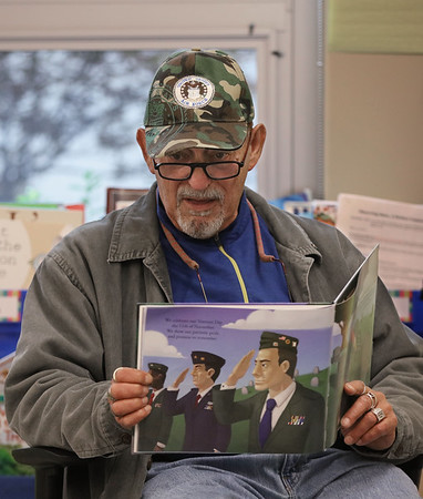 MIKE SPRINGER/Staff photo<br /> Air Force veteran Joe Muse reads a patriotic story Thursday to students in Jodi Parisi's first grade class at West Parish School in Gloucester. Muse is one of a group of veterans visiting Gloucester elementary schools this week to raise awareness of those who have served in the military in preparation for Veterans Day on Monday.<br /> 11/7/2019