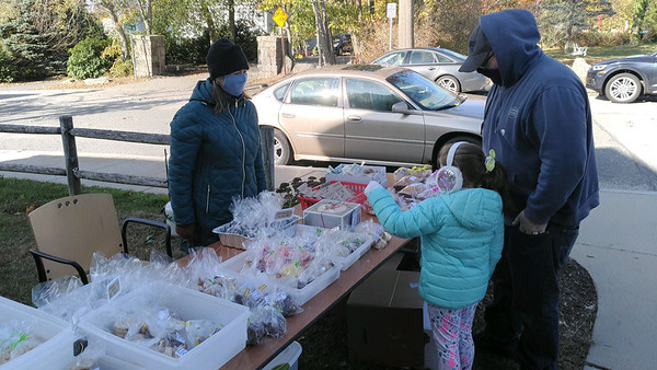 SEAN HORGAN/Staff photo/Hannah Fonti of the West Parish PTO waits on Ian and Savannah Gallant at the bake sale outside the polls at the Magnoilia lLibrary on Lexington Avenue in Gloucester.