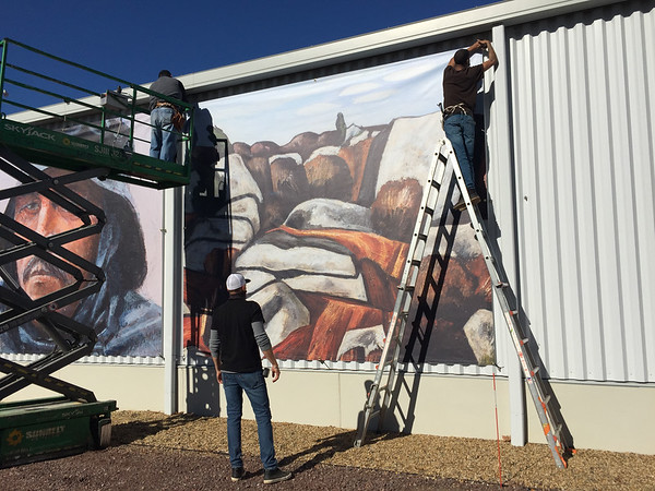 GAIL McCARTHY/Staff photo/Workers place giant canvas banners depicting the works of Cape Ann artists on the Janet & William Ellery James Center at the Cape Ann Museum Green off Grant Circle, the gateway to Gloucester.