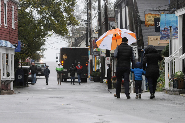 TIM JEAN/Staff photo<br /> <br /> Despite the light rain locals and tourists walk the streets in downtown Rockport.  10/24/18