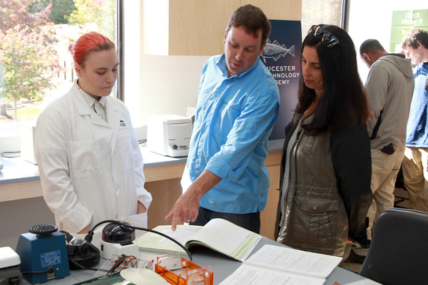 From left to right: Student Madeleine Harlan explaining the program to Gloucester residents Kara and Kevan Stevens at an open house at the new Gloucester Marine Genomics Institute.
