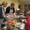 Desi Smith Photo.   Dan McKenna (center) a cook from Short and Main, works with Zoe Karelas (left) of Melrose, Lesley Mello and her son Samuel 8, of Gloucester,peeling pumkins and squash for dumplings and soup,Tuesday night at the Open Door on Emerson Ave, were they and others learn to cook using local harvest.   October 18,2016