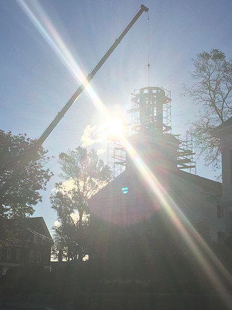 ABIGAIL BLISS/Staff photo/The morning sun shines as Salem-based American Steeple and Tower Company lowers a frame support into the steeple to prepare for sitting First Congregational Church of Rockport's new bell inside.