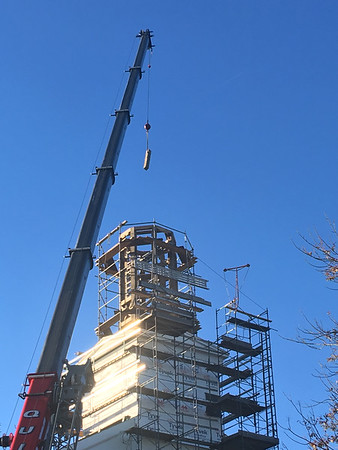 ABIGAIL BLISS/Staff photo<br /> Workers with Salem-based American Steeple and Tower Company use a crane to lift one of two supporting beams from the First Congregational Church of Rockport's lawn and lower it onto the steeple's frame to support a new bell.