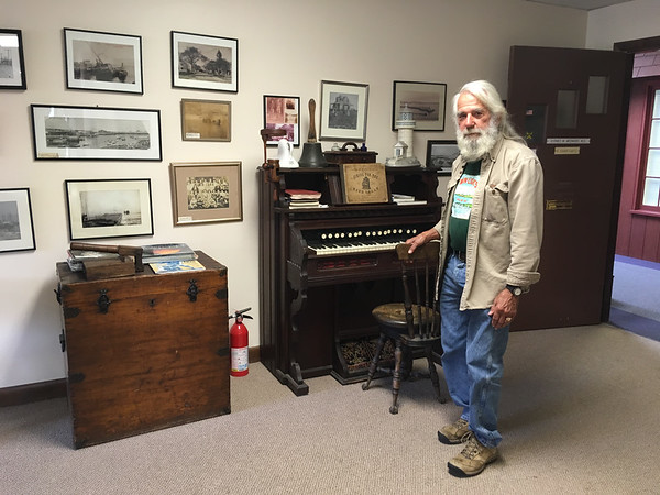 ABIGAIL BLISS/Staff phto/Dr. Sydney Wedmore, a physician in Rockport for 43 years, is retiring later this month. Antiques and historical photos of town decorate his waiting room at the Whistlestop Mall.