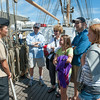 """DESI SMITH/Staff photo.  Cadet """"ensign"""" Tayler Schwamb from Bethel, Connecticut, answers some questions about the 295 ft Coast Guard Tall Ship Eagle, during a public open house, as part of Schooner Festival, saturday morning at Americold, next to Cruiseport in Gloucester. From left to right, are Richard and Betsy Sampson from Winchester,Ma, here visiting their son Lou Sampson and his daughters Clair 11, and Anna 13, of Gloucester. August 30,2014"""