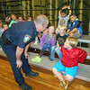 SEAN HORGAN/Staff photo/Gloucester police Lt. Jeremiah Nicastro answers a question from Finnian Runnels, a first-grader at East Gloucester Elementary School, during the announcement that three Gloucester patrolmen have adopted all of the first-graders in Gloucester public schools in an expandsion of the department's community outreach program, Kops N Kids.