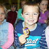 SEAN HORGAN/Staff photo/Cameron Curcuru, a first-grader at East Gloucester Elementary School, is the envy of his classmates as he holds the badge of Gloucester police Lt. Jeremiah Nicastro after learning that three Gloucester patrolmen, as part of a an expansion of the department's Kops N Kids community outreach program, have adopted all the first-graders in the Gloucester  public schools.