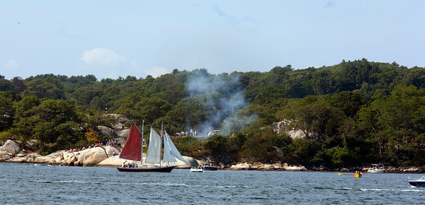 AMY SWEENEY/Staff photo.<br /> The Eileen Marie, out of Boston, a red hulled centerboard schooner, sails by Stage Fort Park as the canons go off during the Parade of Sail in the 33rd annual Gloucester Schooner Festival.<br /> Sept. 4, 2017