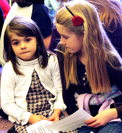 Allegra Boverman/Gloucester Daily Times. During the final assembly at the Gloucester Community Arts Charter School on Wednesday morning. From left are kindergarten student Hannah Olson and fourth grader Cara Buchanan share their favorite things about being at the school and what they look forward to at their new school.