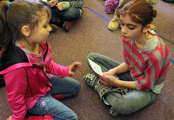 Allegra Boverman/Gloucester Daily Times. During the final assembly at the Gloucester Community Arts Charter School on Wednesday morning. Students could share their favorite memories about being at the school and what they'll miss, plus what they look forward to at their new school. Older students and younger students paired up to talk about these things. From left are Caishalyn Lorentzen and Jessica Amaral.