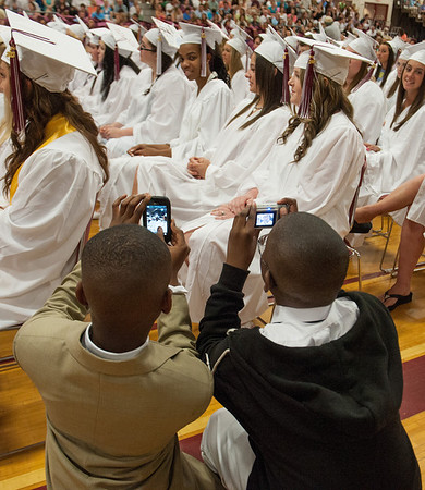 Desi Smith/Gloucester Daily Times.  Shay Wesley-Palmer and Justin Fenton kneel down together to take a photo of their cousin Sashjenelle Ince, as she waits to receive her deploma at the graduation of GHS Class of 2013 Sunday afternoon in the Benjamin A Smith Fieldhouse.       June 9,2013
