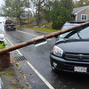Gloucester: A worker from National Grid cuts the power from a metal pole that chashed onto a car driven by Jay Fronterio of Gloucester as his wife far left, a passenger in the car looks on. Fronterio and his wife were forced to make a u-turn on Atlantic Rd by Souther Rd because of road closures due to the storm. The couple escaped serious injury when the sun roof exploded showering them with glass.  Desi Smith/Gloucester Daily Times. October 29,2012.