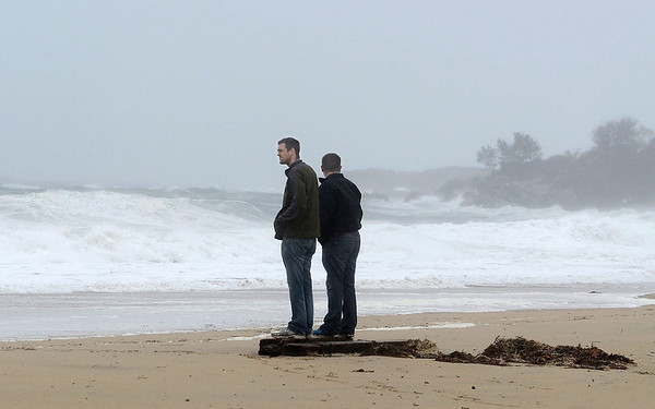 MIKE SPRINGER/Gloucester Daily Times<br /> Two men look out at the rising surf from Hurrican Sandy near high tide late Monday on Singing Beach in Manchester.