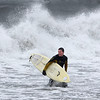 MIKE SPRINGER/Gloucester Daily Times<br /> William Lawther of Lanesville walks into the shore after surfing high waves driven by Hurricane Sandy on Monday afternoon at the town beach in Magnolia.