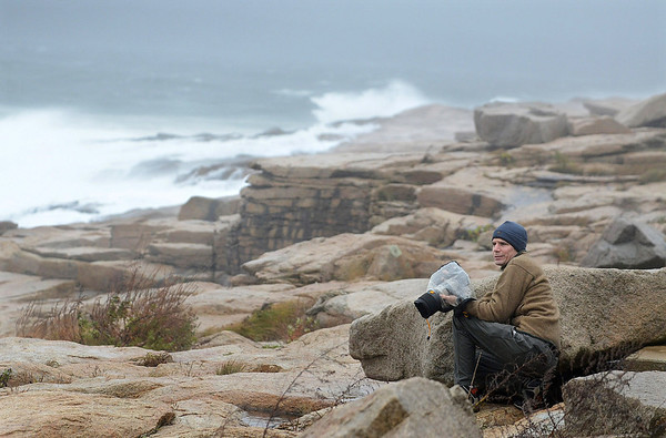 MIKE SPRINGER/Gloucester Daily Times<br /> Photographer Saul Schor of Rockport huddles against a rock to protect himself from powerful winds from Hurricane Sandy while photographing the surf Monday afternoon in Rockport.