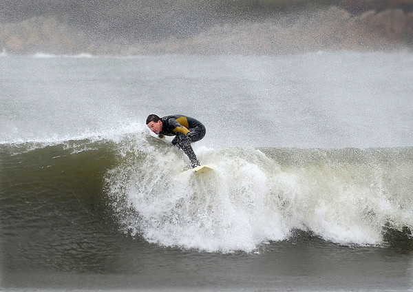 MIKE SPRINGER/Gloucester Daily Times<br /> William Lawther of Lanesville rides a wave off the Magnolia town beach as Hurrican Sandy hit the area Monday afternoon.