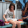 MARIA UMINSKI/Gloucester Daily Times. Friends Mariah Colbert, age 11, of Gloucester and Kimmy Curcuru-Henry, age 11, of Rockport, munch on their lobster lunches from Roy Moore on Bearskin Neck.