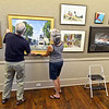 Gloucester: Ray Crane and Beverly Palmacci hangs one of Artist Ken Knowles paintings at the North Shore Art Association Saturday afternoon. Ray and Beverly are members of the Norh Shore Art Association who helped set up for the Live Art Auction which is set for August 11.  Desi Smith/Gloucester Daily Times. August 4,2012
