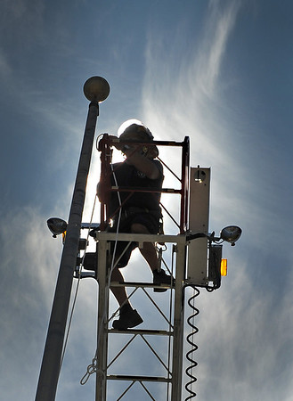 Gloucester:  Gloucester Firefighter Greg Marchant replaces one of three ropes on the flag poles at the Gloucester High School Monday morning. Desi Smith/Gloucester Daily Times. August 20,2012
