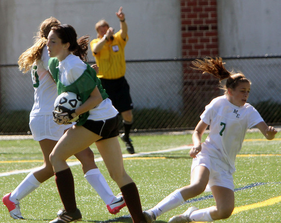 ALLEGRA BOVERMAN/Gloucester Daily Times From left are Gloucester's Riley Gately, and behind and at left are Manchester-Essex players Rachel Daley and Bella Mastendino in action during their scrimmage in Manchester on Wednesday afternoon. Gloucester beat M-E 2-1 in overtime.