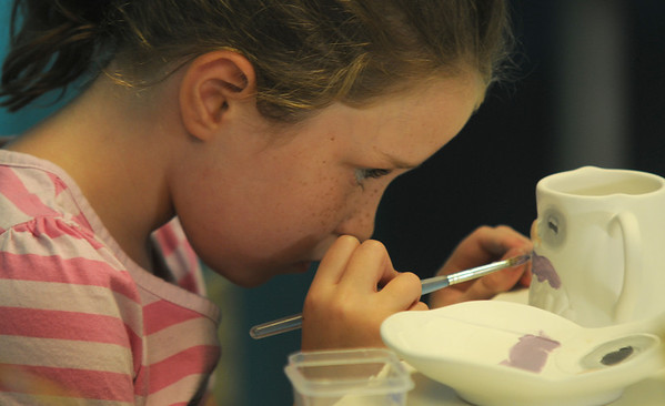 """JIm Vaiknoras/Gloucester Daily Times. Ella Costa, 6, paints a cup shaped like an owl at the """" Give A Hoot"""" summer art program at Glazed in Gloucester for kids in Kindergarten through 8th grade held tuesdays through friday mornings."""