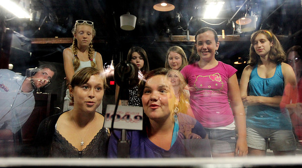 ALLEGRA BOVERMAN/Staff photo. Gloucester Daily Times. Gloucester: Gloucester Stage Company's Youth Acting Workshop participants learned about radio broadcasting on Friday at the theater with staff from North Shore 104.9 radio. Reflected in the glass of a portable recording booth are from left: Jay Foss, who does production for the radio station, Heidi Dallin, director of the YAW program, and Aurelia Nelson, radio account executive. The students learned about the history of radio, voice technique, scripts, and they rewrote and performed a script, read parts and recorded pieces for use on the radio station. In front, seated  from left are: Jaqi McCarthy, 15 and Talia DeWolfe, 12. In back from left are:  Sierra Rudolph, 13, Alexandra Grace, 14, Sophia McLean, 12, Jessyca Muniz, 12, and Evanthia Boling, 16.