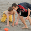 Jim Vaiknoras/Gloucester Daily Times: Nate Shepard, yellow shorts,  and Andrew Mente  reach for a loose ball while playing a game of touch football on Good Harbor Beach this past week. It was Andrew's 16th birthday and he wanted to play 2 on 2 football with his friends Nate and John Dyer and his dad Nathan Mente.