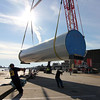 Allegra Boverman/Gloucester Daily Times. Pieces of one wind turbine destined for Gloucester Engineering in the Blackburn Industrial Park arrived by barge on Tuesday to Cruiseport. Three large pieces were unloaded and will be moved, base first, on Wednesday, Thursday and Friday. The blades will arrive later on by truck from Pennsylvania. Working with the base as it's moved from the barge to the Cruiseport parking lot are, from left, Jason Jenkins, an ironworker with Local 6, and Shannon Foose, an ironworker with Local 7.