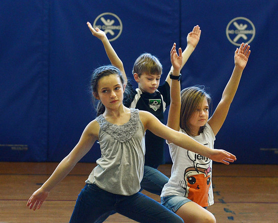 """MIKE SPRINGER/Gloucester Daily Times<br /> From left, fifth grader Sofia Gillespie, Fourth grader Pieter Breuker and fourth grader Grace Swanciger strike poses while playing a game in the Manchester Parks and Recreation Department """"Yoga for Kids"""" program recently at Manchester Memorial Elementary School. The program, which incorporated games, music, stories and crafts to help children learn yoga poses and breathing techniques, was taught by Suzanne Otterbein of Manchester. According to the Parks and Recreation brochure, """"Yoga will help your child to increase flexibility and strength, enhance concentration skills, improve general well-being, feel physicall and mentally rejuvenated, boost confidence, relax the mind and reduce stress."""""""
