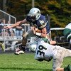Hamilton-Wenham: Manchester's Henry Gedney grabs the leg of a leaping Trevor Lyons at Hamilton-Wenham High School Saturday afternoon .Desi Smith/Gloucester Daily Times. October 20,2012.