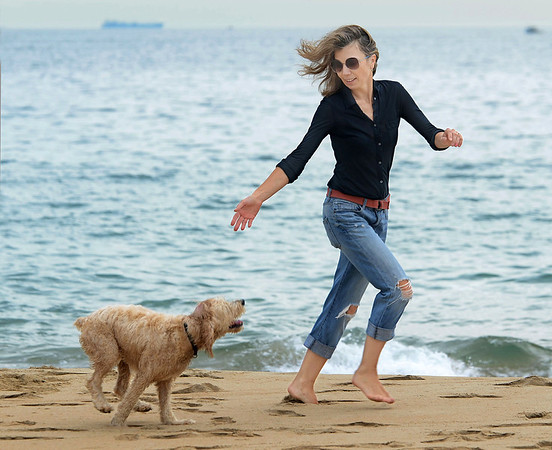 Mike Springer/Gloucester Daily Times<br /> Anna Gamota of Lexington runs with her dog Max Tuesday, Oct. 2, 2012 on Singing Beach in Manchester.
