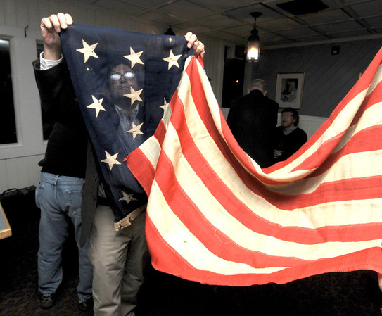 Jim Vaiknoras/Gloucester Daily Times: Michael Bider of Essex looks over a flag with 13 stars at the 4th annual Essex Antiques Appraisal Night At Periwinkles Restaurant. Bider believes the flag is from the centenial in 1876.