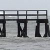 MIKE SPRINGER/Gloucester Daily Times<br /> A surfer jumps off the Magnolia pier with his surfboard Monday afternoon as Hurricane Sandy pounded the region.