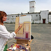 Allegra Boverman/Gloucester Daily Times Laureen Adrienne Maher of East Gloucester was starting a painting study of the Birdseye Building on Commercial Street on Thursday. She wants to do a series of paintings of each quadrant of the building and has taken many photos of the site. She wants to make sure she can paint the building before it could be torn down.