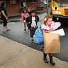 Gloucester: Par Educator Brenda Silveira upper left, greets students as they get off the bus on their first day back at West Parish School Wednesday morning. Some students brought  more than enough to start the school year. Desi Smith/Gloucester Daily Times. September 5, 2012