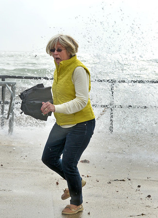"Desi Smith/Gloucester Daily Times. Rockport: Taken by surprise, Priscilla Khachadoorian of Rockport runs away from a wave that's about to soak her and friend Dianne Glennon, who moved out of the way just a little bit faster while watching the waves and viewing the dead fin whale that was near Cape Hedge Beach at the end of October.<br /> <br /> ""I love this woman's reaction as she runs from a crashing wave that catches her off guard during Hurricane Sandy."""