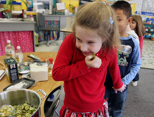 """ALLEGRA BOVERMAN/Staff photo.Gloucester Daily Times. Gloucester: FoodCorps and CitySprouts hosted """"Pickle Pioneer"""" day at Veterans Memorial Elementary School in mid-February. The kindergarten class taught by Janet Allen actually made pickles out of cucumbers and onions. Sampling them, from front to back are: Brigitte Lawson, Wilson Ortiz and Abigail Doucette. Brigitte wasn't sure she liked their taste.<br /> <br /> """"Watching students doing unusual hands-on learning activities at school in their classrooms is one of my favorite things to photograph for the newspaper. I am constantly in search of these opportunities; and when I heard that children in one class at Veterans Memorial Elementary School in Gloucester were learning how to make pickles together, I made it my business to be there. Knowing that some kids have picky taste buds, I was curious about their reactions to the taste of their freshly made pickles."""""""