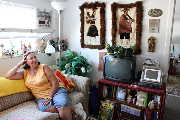 """MARIA UMINSKI/Gloucester Daily Times. Resident Mary Ann Camp relaxes in her home at Rockport High School Apartments in August.<br /> <br /> """"The one thing I loved about taking pictures of the residents who live in the Rockport High School Apartments was not only seeing their lovely living spaces but hearing their stories. Whether they had lived in Rockport all their lives and attended school in that very building or if they had moved there, it all fascinated me. Also the fact that it was once a high school is still pretty cool to me."""""""