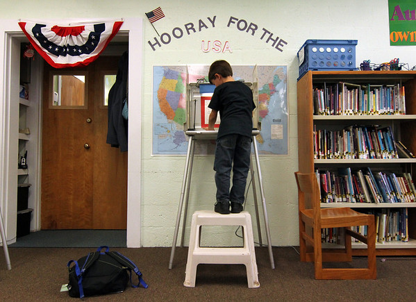 "ALLEGRA BOVERMAN/Staff photo. Gloucester Daily Times. Students at Memorial Elementary School in Manchester were participating in a mock Election Day the friday before Election Day in November. First grader Dominic Tiberii, standing high on a stepstool to reach the voting booth, casts his vote for president. President Barack Obama won amongst the student population, over candidate Mitt Romney.<br /> <br /> ""The mock elections held at Manchester Memorial Elementary School were a joy to behold. The voting booths were lent by the town and some pupils needed stepstools to reach the writing surface. They had enthusiastically studied all the platforms, researched all the candidates, learned about the process. The library was decorated for the occasion, including lots of books on display about the presidents, the electoral college and other voting topics. One student had to vote before leaving early; for that moment, the library was silent and nearly empty. He carefully stepped up onto the stool and spent some time considering his vote. Doing one's civic duty, no matter how young, delighted me."""
