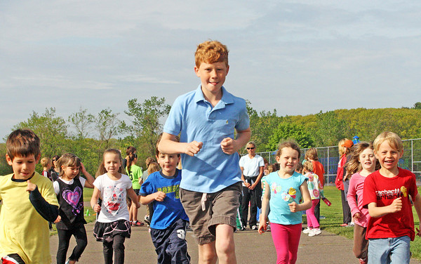Jesse Poole/Gloucester Daily Times. Rockport: Fifth-grader Will Andrews paces a group of joyful kindergarteners for a one mile run during running club  in mid-May at Rockport Elementary School. Many of these students were preparing for the upcoming Motif No. 1 Day 5K and 1 Mile Fun Run.