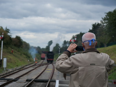 Old man shooting video of steam engine