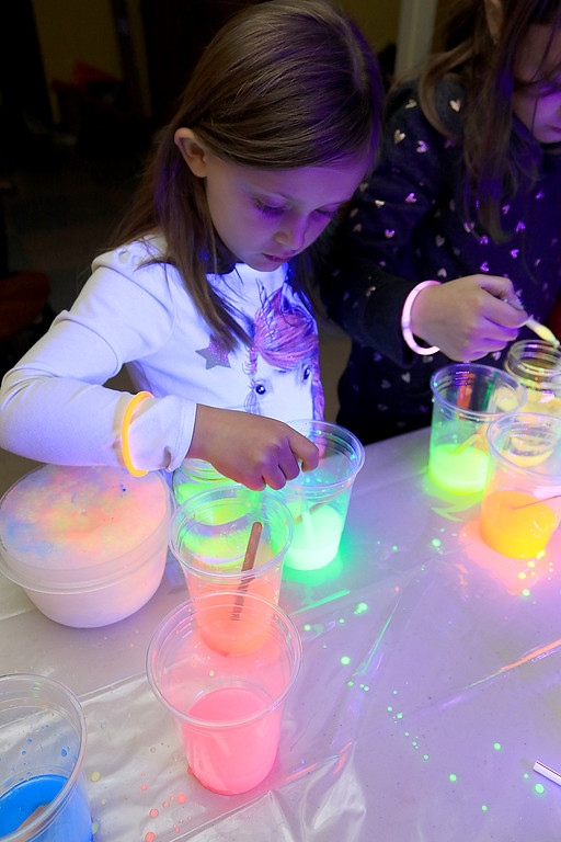 . Stevens Memorial Library held a Glow Party on Wednesday night in their Activity Room for kids 5-12. The kids mixed baby oil with glow in the dark paint and water during the event. Addison Holme, 6, plays with the mixtures. SENTINEL & ENTERPRISE/JOHN LOVE
